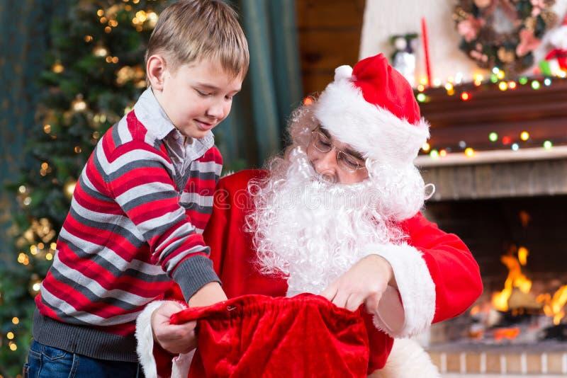 给一个礼物从大袋的圣诞老人到孩子 免版税库存图片