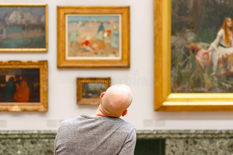 一个秃头人赞赏的绘画的后面看法被显示在塔特Bri 免版税库存图片