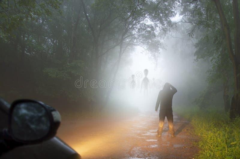 一个科幻概念:一个男人看着夜间雾霭笼罩的阴森森林道上的外星人 海莱特 免版税库存照片