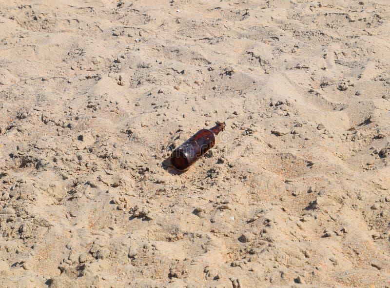 一个空的瓶啤酒在沙子说谎 图库摄影