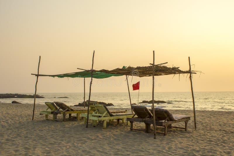 一个空的老木海滩懒人在海洋的沙滩的一个棕榈机盖下在晚上 在沿海的红旗 库存图片
