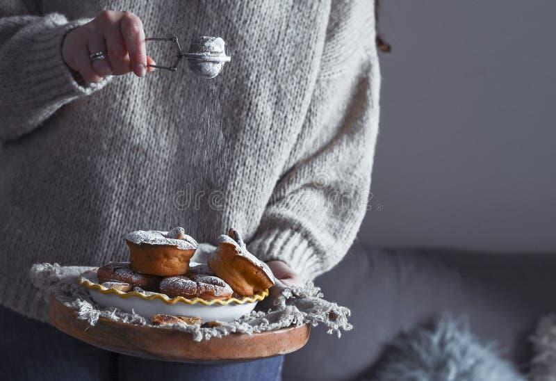一个穿毛衣的女人手里拿着糖霜 生活风格的舒适照片 木制糕点 库存照片