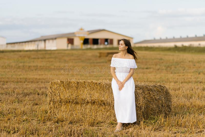 一个穿白色裙子的女孩站在田地里一堆稻草旁 免版税库存图片