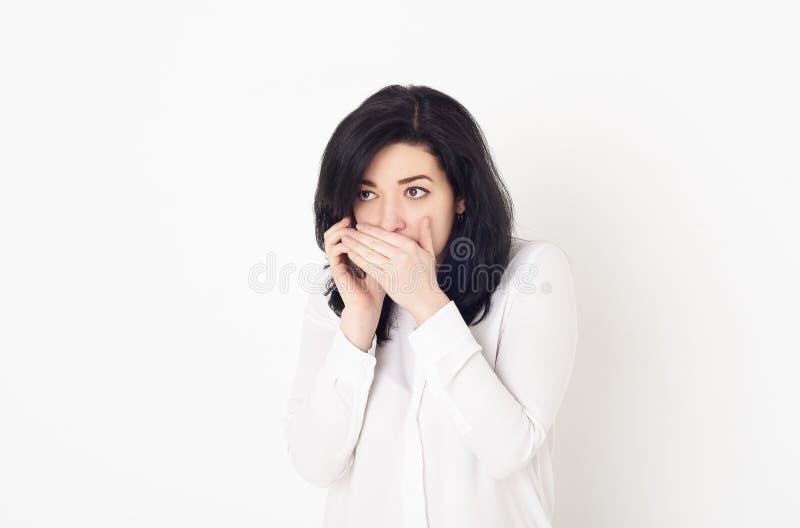 一个穿白衬衫的小女孩正在打电话,用手捂住嘴 她告诉一个秘密,或者重新告诉 免版税库存图片