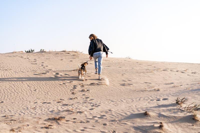 一个穿皮夹克和蓝色牛仔裤的白种女孩带着猎犬在沙滩上跑来跑去 免版税库存图片