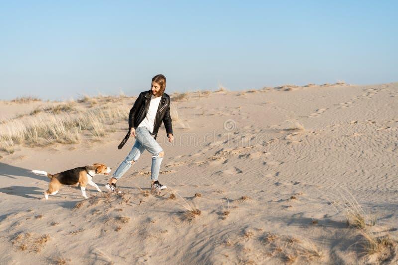 一个穿皮夹克和蓝色牛仔裤的白种女孩带着猎犬在沙滩上跑来跑去 库存图片