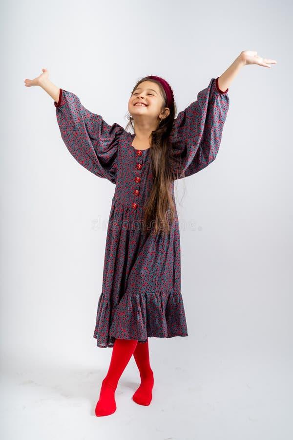 一个穿着灰色连衣裙、花色鲜艳、红色纽扣、穿红色紧身衣的孩子,在白色背景中被隔离 免版税库存照片
