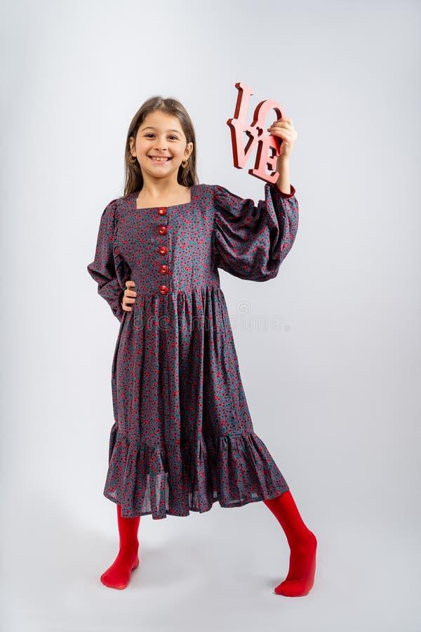 一个穿着灰色连衣裙、花色鲜艳、红色纽扣、红色紧身衣、手上铭文爱意的孩子,被隔离在白色上 免版税库存图片