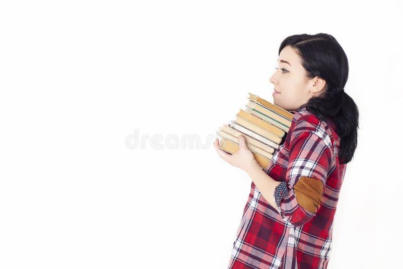 一个穿红格子衬衫,背着一堆旧书,旧课本的年轻女学生 准入准备 免版税库存照片