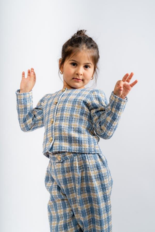 一个穿蓝白色衬衫、格子衬衫和白色背景上的蓝白格子裤子的孩子 免版税库存图片