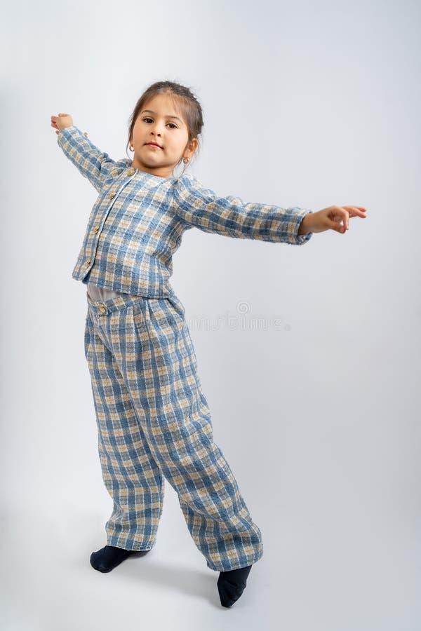 一个穿蓝白色衬衫、格子衬衫和白色背景上的蓝白格子裤子的孩子 库存照片