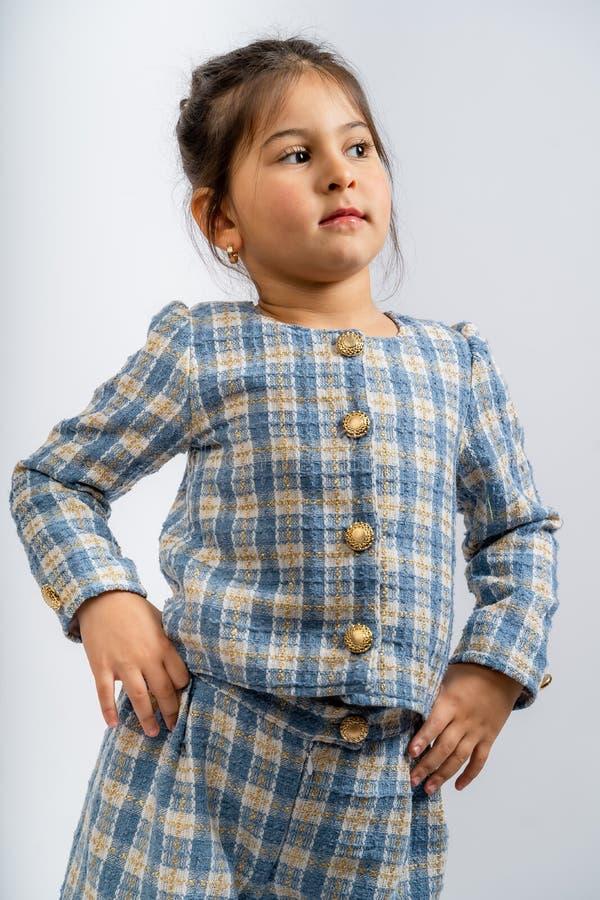 一个穿蓝白色衬衫、格子衬衫和白色背景上的蓝白格子裤子的孩子 图库摄影