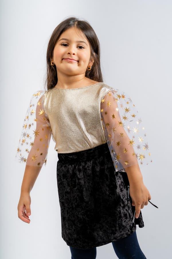一个穿金色衬衫、透明袖子、黑色灯芯绒裙子和白色背景中突显的蓝色紧身衣的孩子 图库摄影