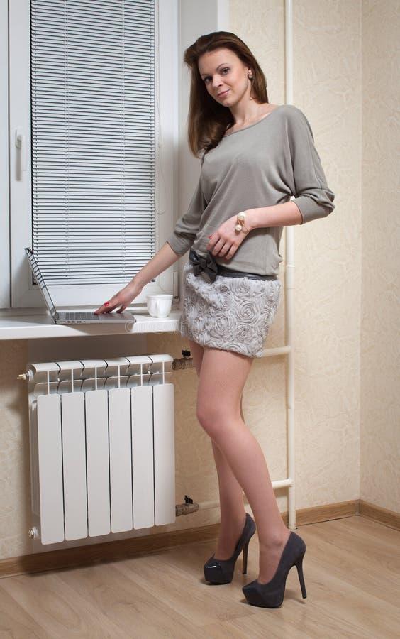 一个窗口的好金发碧眼的女人与膝上型计算机 图库摄影