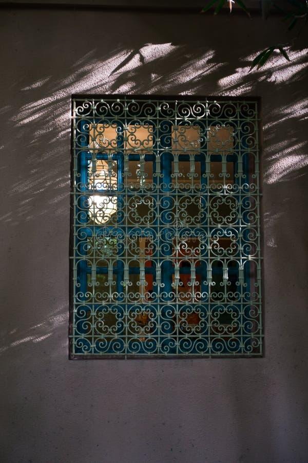 一个窗口的建筑细节与东方篱芭的在日落在Majorelle庭院,马拉喀什,摩洛哥里 图库摄影