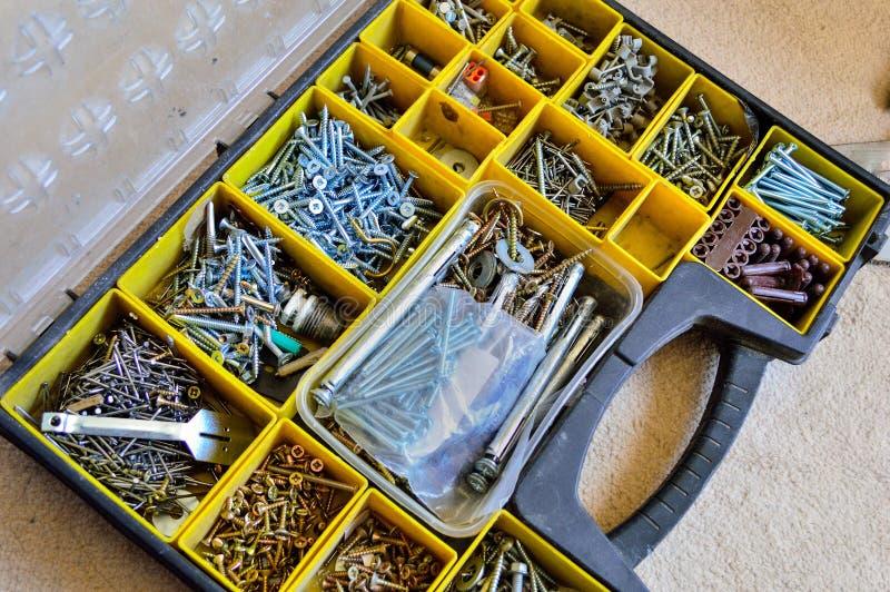 一个箱子以钉子、螺丝、坚果、螺栓和洗衣机品种  免版税库存图片