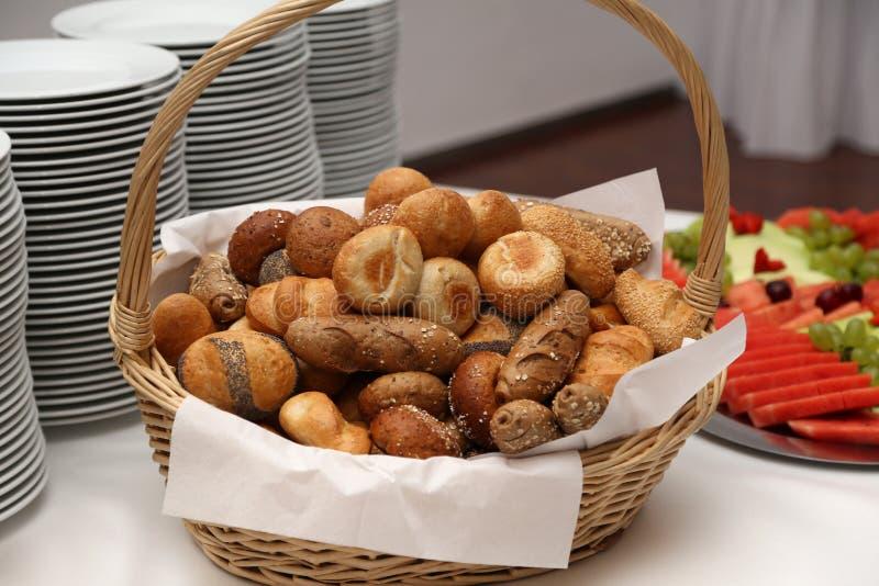 一个篮子用新鲜的小圆面包在桌上 免版税库存图片