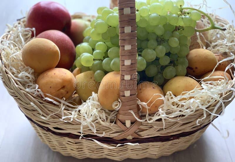 一个篮子用美丽的果子 美丽的橙色杏子和白葡萄 免版税库存照片