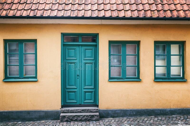 一个米黄大厦的门面与一绿色门、背景和tex的 库存图片