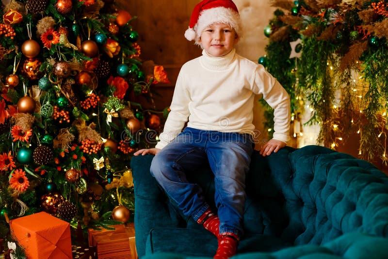 一个米黄被编织的毛线衣和圣诞老人的红色盖帽的一个七岁的男孩坐一个绿色沙发在圣诞节屋子 免版税库存照片