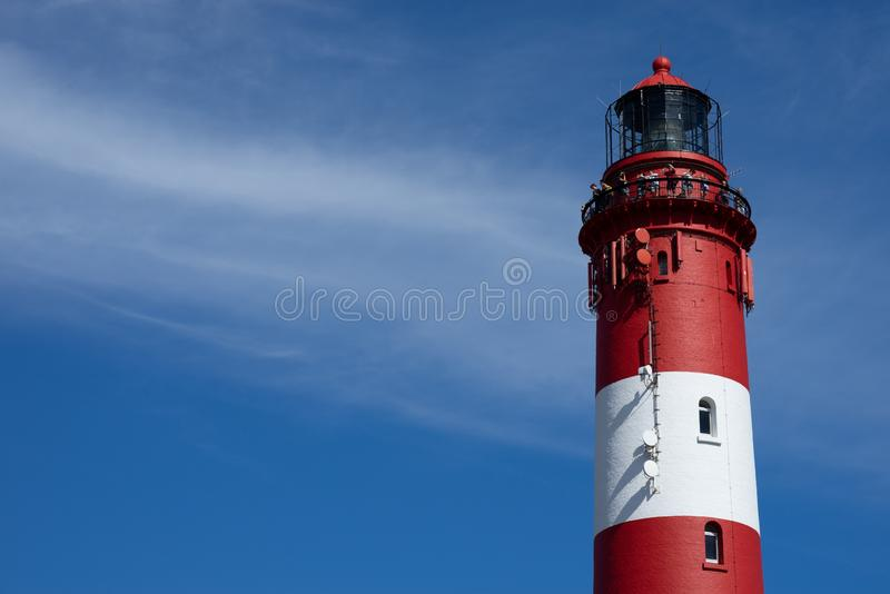 一个红色和白色灯塔塔的上面的美丽的宽射击在海滩的一好日子 图库摄影