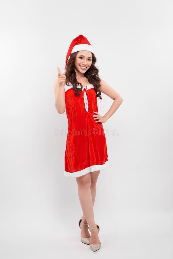 一个红色圣诞老人帽子的妇女有在一个惊奇的表示的配比的唇膏的,隔绝在与拷贝空间的白色您的文本的 图库摄影