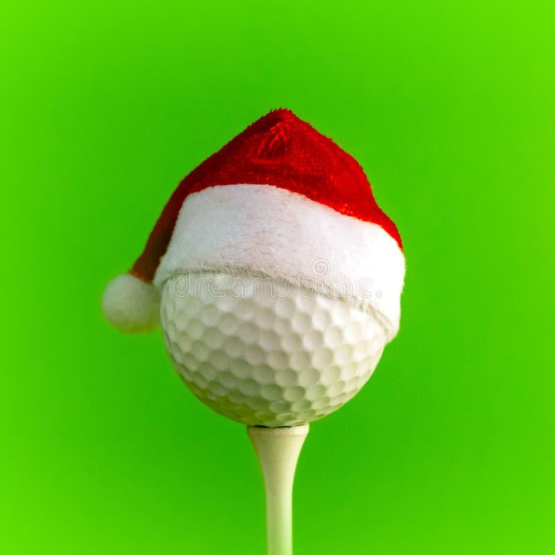 一个红色圣诞老人项目帽子在发球区域登上的高尔夫球戴 鲜绿色的背景 具体化或说明的方形的框架 免版税图库摄影