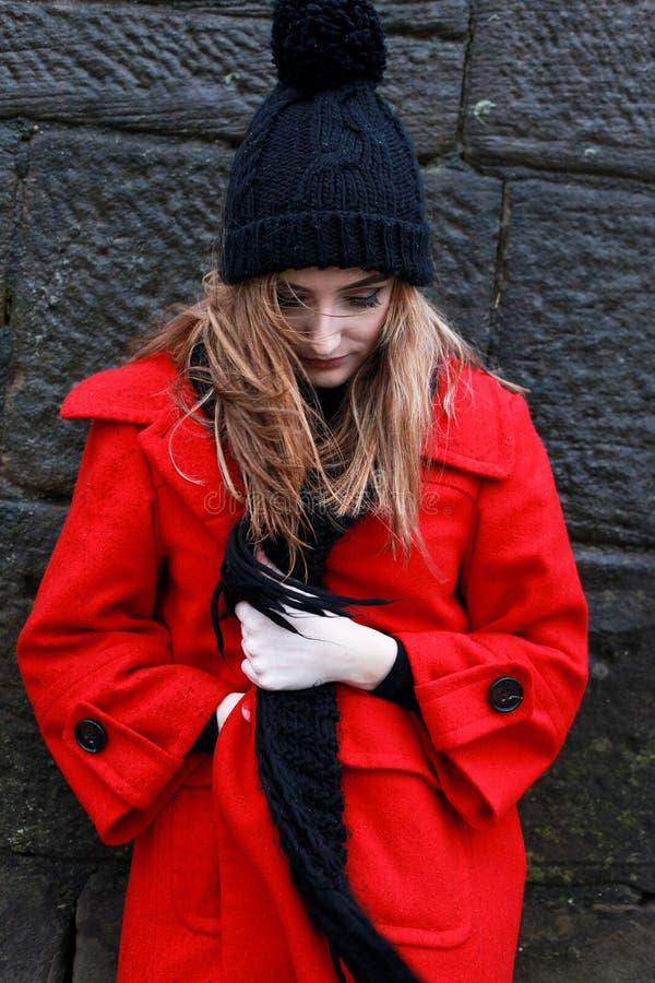 戴一个红色夹克和pom pom帽子的妇女 图库摄影