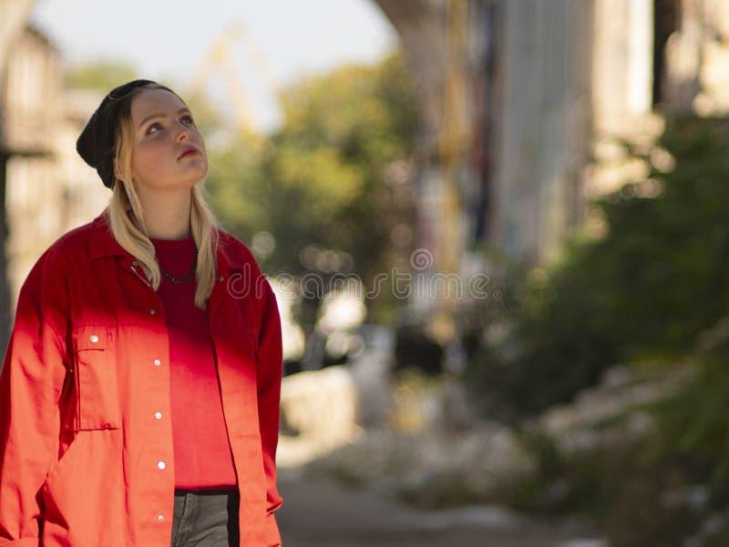 一个红色夹克身分的可爱的年轻女性白肤金发的少年在街道上 免版税库存图片