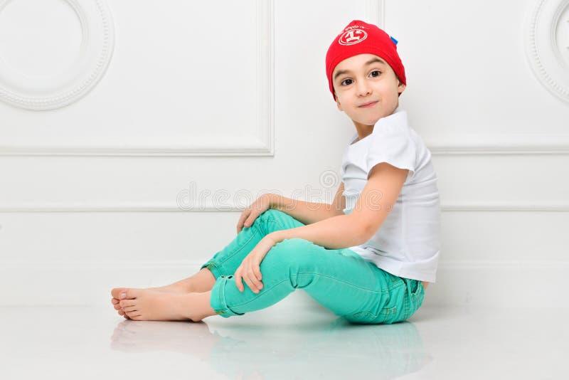 一个红色帽子和牛仔裤的时髦的小男孩在白色背景在演播室 r 免版税库存照片