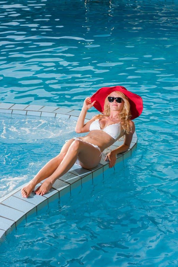 戴一个红色帽子的妇女坐在水池 图库摄影