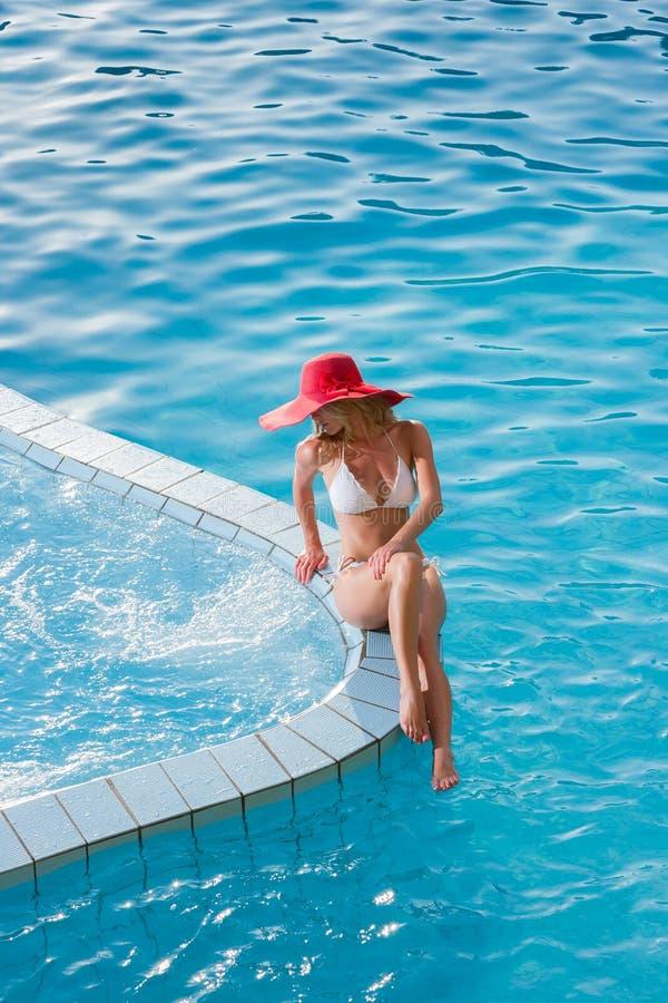戴一个红色帽子的妇女坐在水池 免版税库存照片