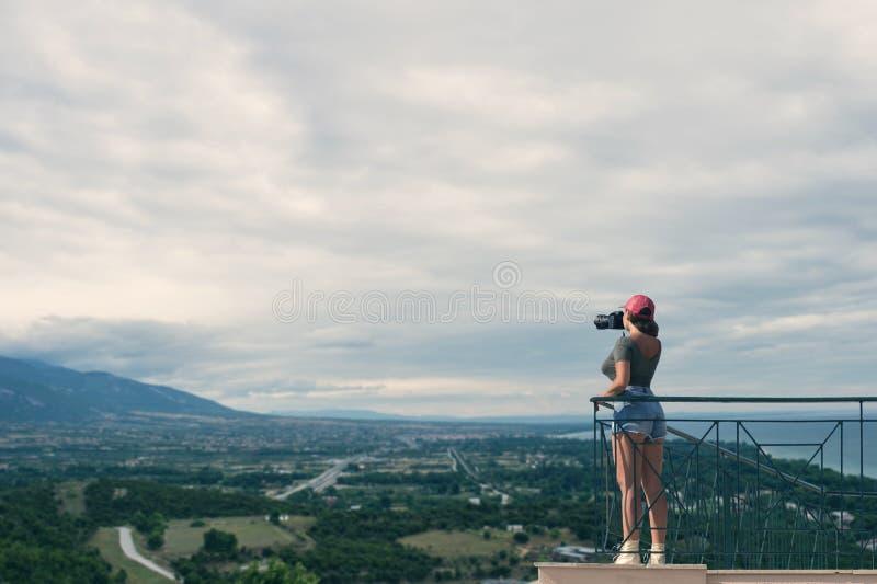 一个红色盖帽的一位女性摄影师有照相机的在希腊市的阳台对面站立卡泰里尼在日落 卡泰里尼 库存照片