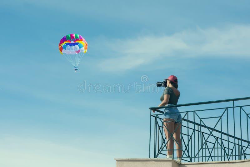 一个红色盖帽的一位女性摄影师有照相机的在蓝天对面的阳台站立与云彩和降伞 妇女采取pi 免版税库存照片