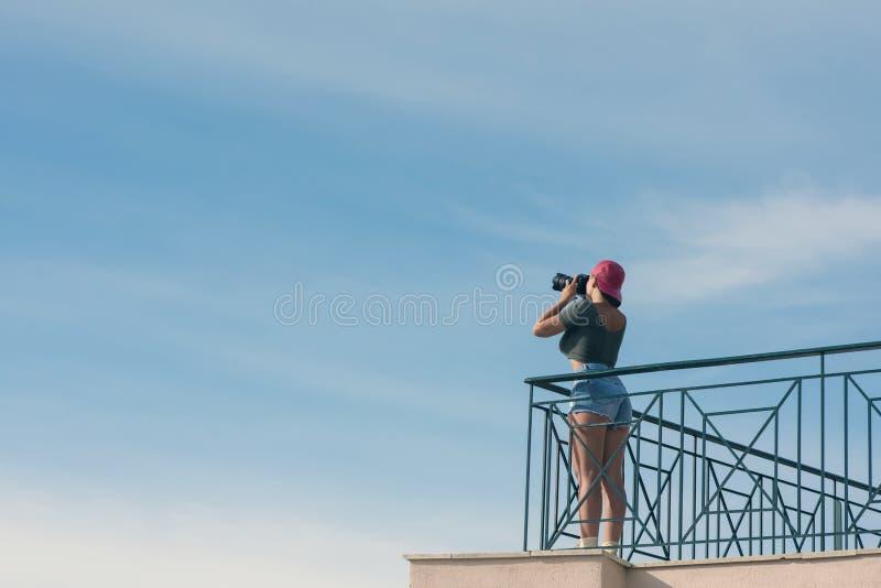 一个红色盖帽的一位女性摄影师有照相机的在蓝天对面的阳台站立与云彩 妇女为天空照相 库存照片