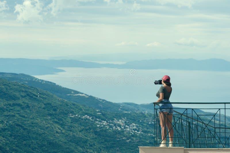 一个红色盖帽的女性摄影师有照相机的在希腊市的阳台对面站立沃洛斯在日落 沃洛斯希腊 库存图片