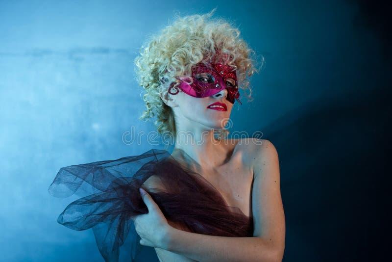 一个红色面具的美丽的性感的女孩金发碧眼的女人在演播室坐蓝色背景 免版税库存图片