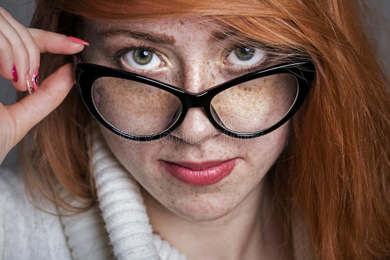 一个红头发人有雀斑的女孩的画象玻璃的 库存图片