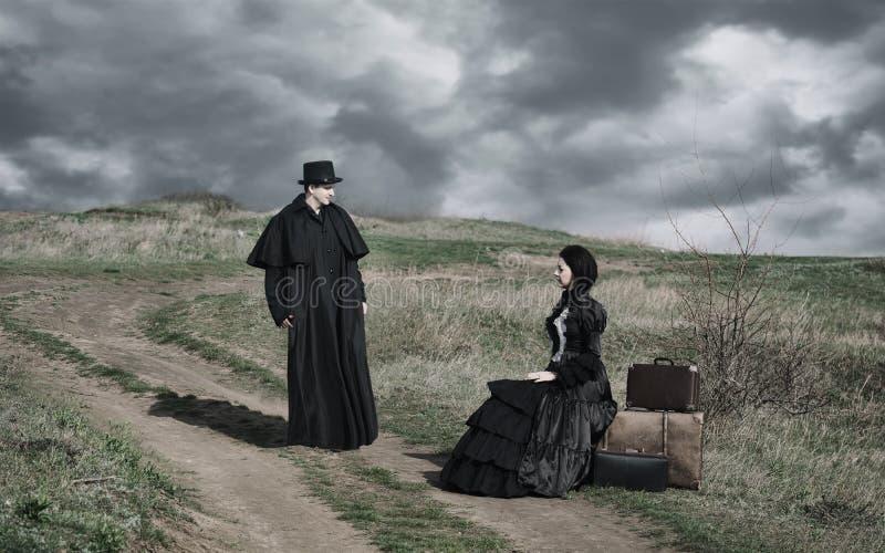 一个维多利亚女王时代的夫人的画象黑开会的在有附近站立她的行李和的绅士的路 图库摄影