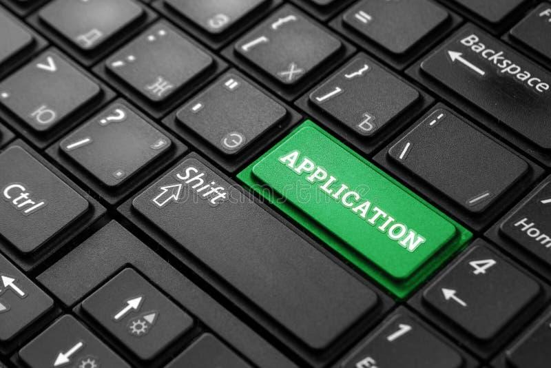 一个绿色按钮的特写镜头有词应用的,在一个黑键盘 r 概念 图库摄影