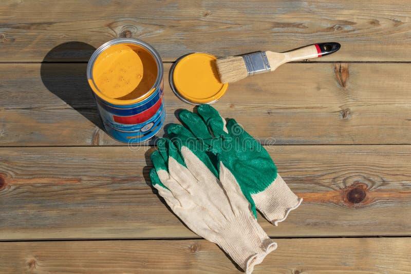 一个罐头与刷子和手套的黄色油漆,准备好绘 修理和整修概念,顶视图 库存图片