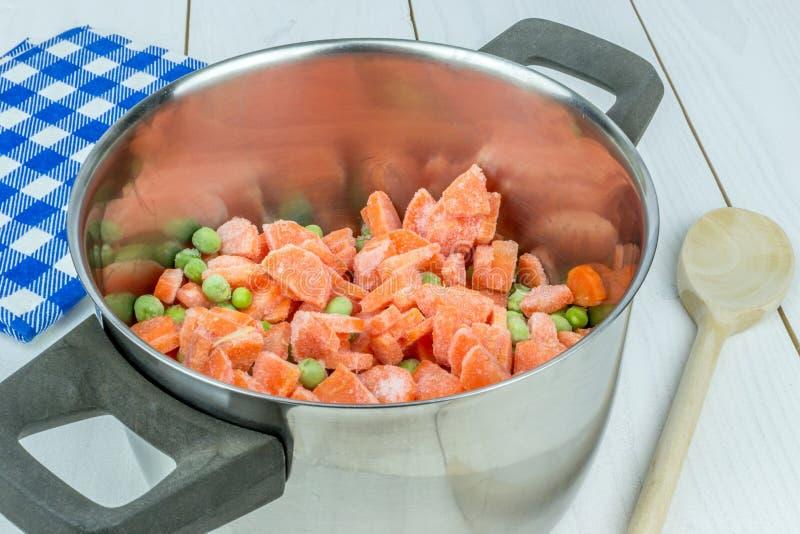 一个罐用冷冻豌豆和红萝卜 库存图片
