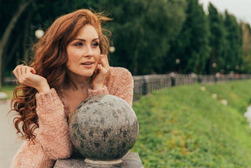 一个美丽和可爱的女孩的画象在公园,有穿着考究,红色头发的,护发, 库存图片