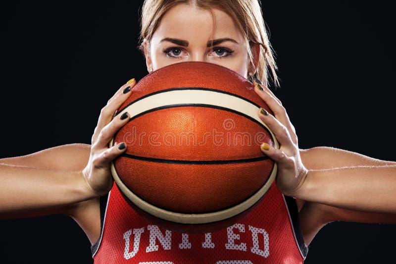 一个美丽和性感的女孩的画象有篮球的在演播室 在黑背景隔绝的体育概念 库存图片