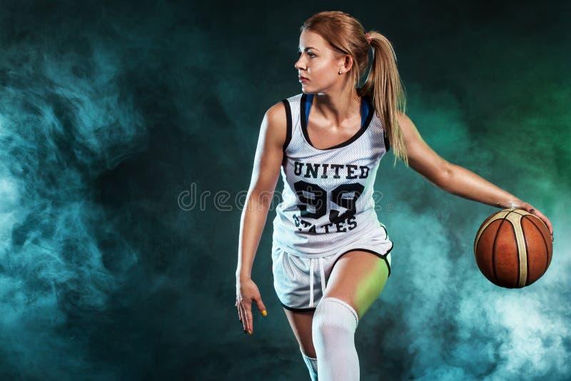 一个美丽和性感的女孩的画象有篮球的在演播室 概念查出的体育运动白色 免版税库存照片
