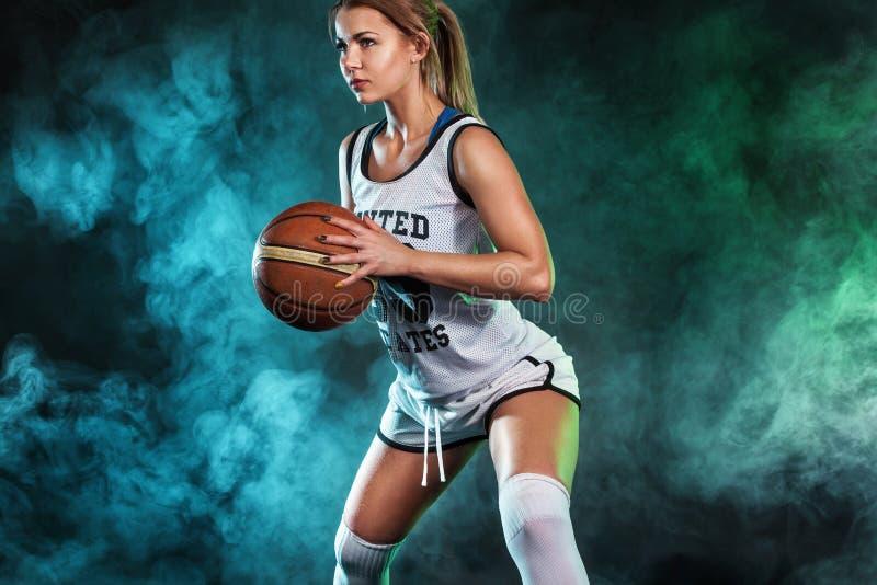 一个美丽和性感的女孩的画象有篮球的在演播室 概念查出的体育运动白色 库存照片