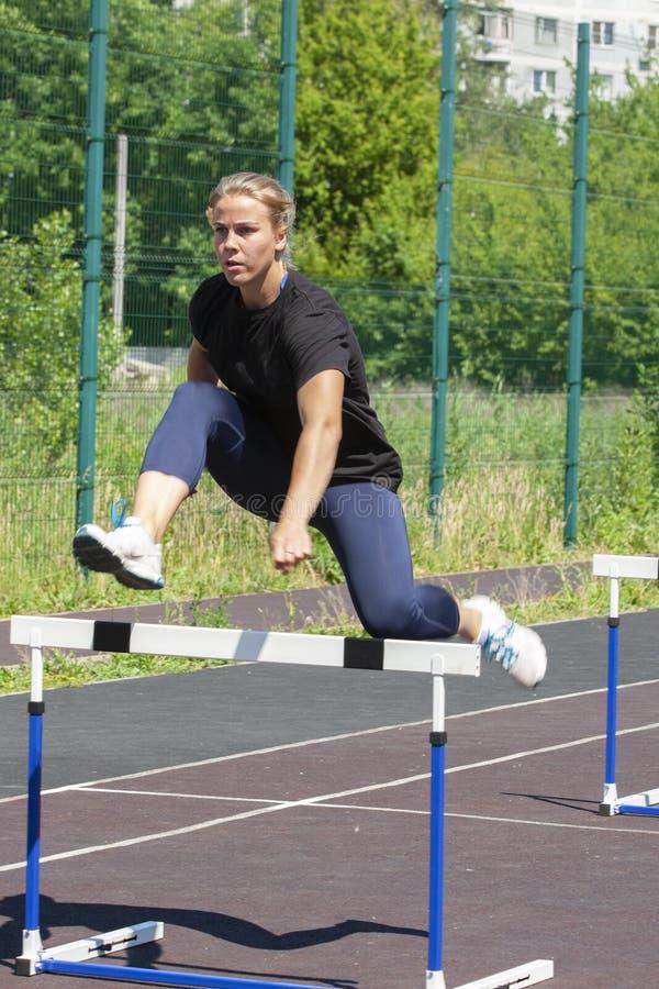 一个美丽和运动女孩在体育场内跑障碍 免版税图库摄影