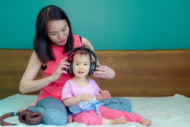 一个美丽的亚裔夫人母亲怀孕 采取来临的一个大耳机到胃让腹部的孩子听有小 免版税库存图片
