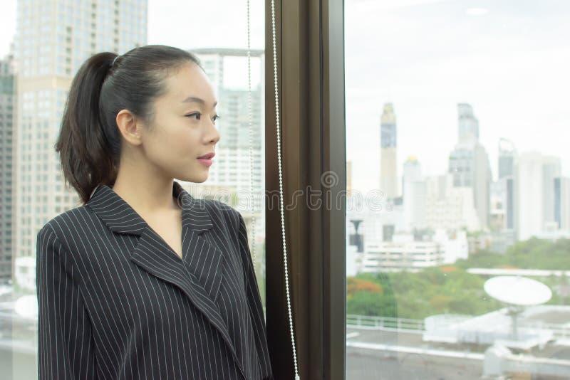 一个美丽的亚裔女商人看看法外面 图库摄影