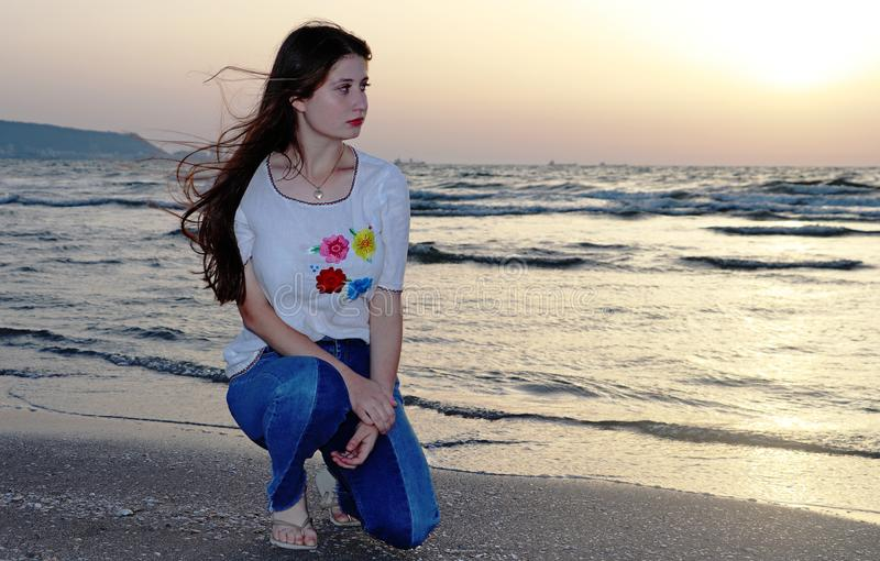 一个美丽的十几岁的女孩坐海滩 免版税库存照片